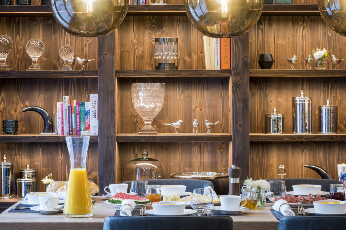 Breakfast table and bookshelves in dining area at Apartment Balegia in Lech