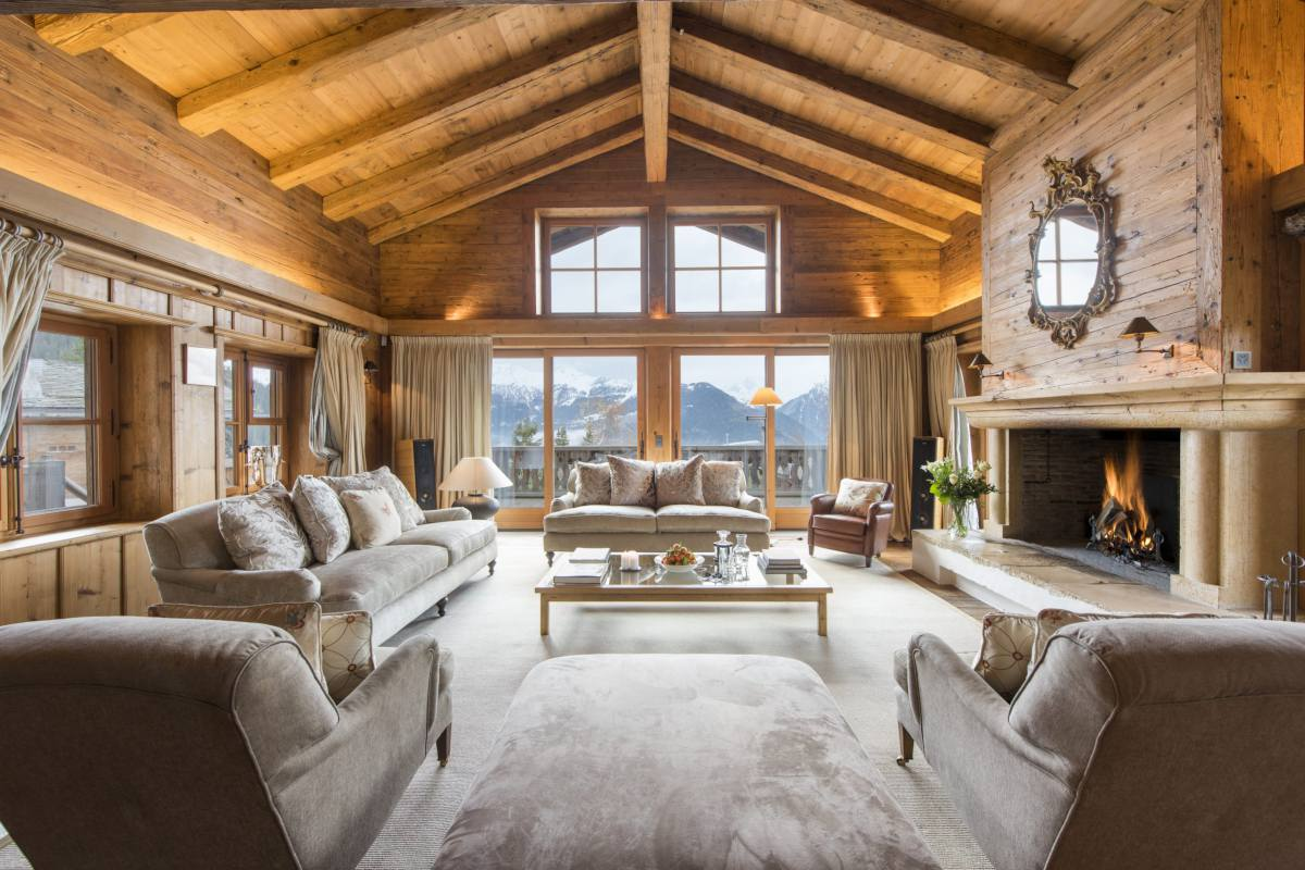 Main chalet living room with stone fireplace and mountain views at Bella Coola Estate in Verbier