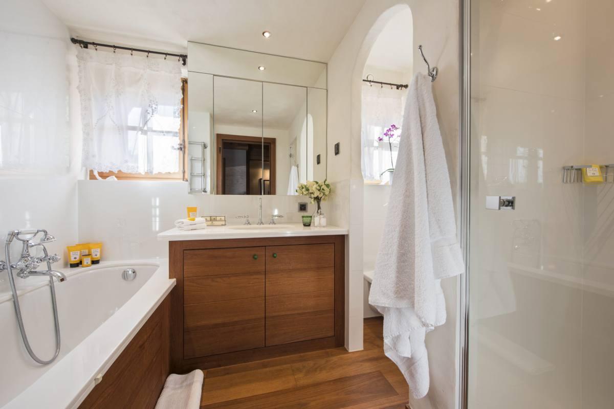 En suite bathroom with bathtub and separate shower at Chalet Bella Coola in Verbier