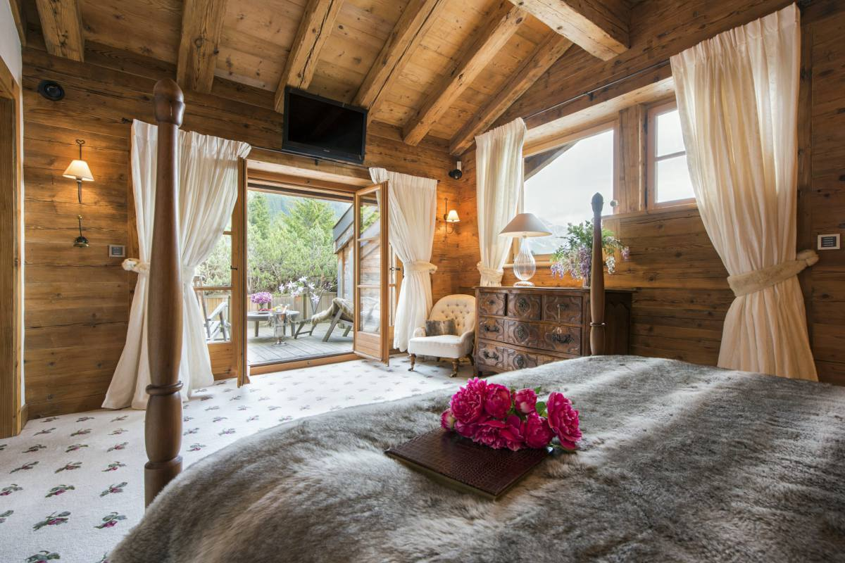 Master bedroom with views onto private balcony at Chalet Bella Coola in Verbier