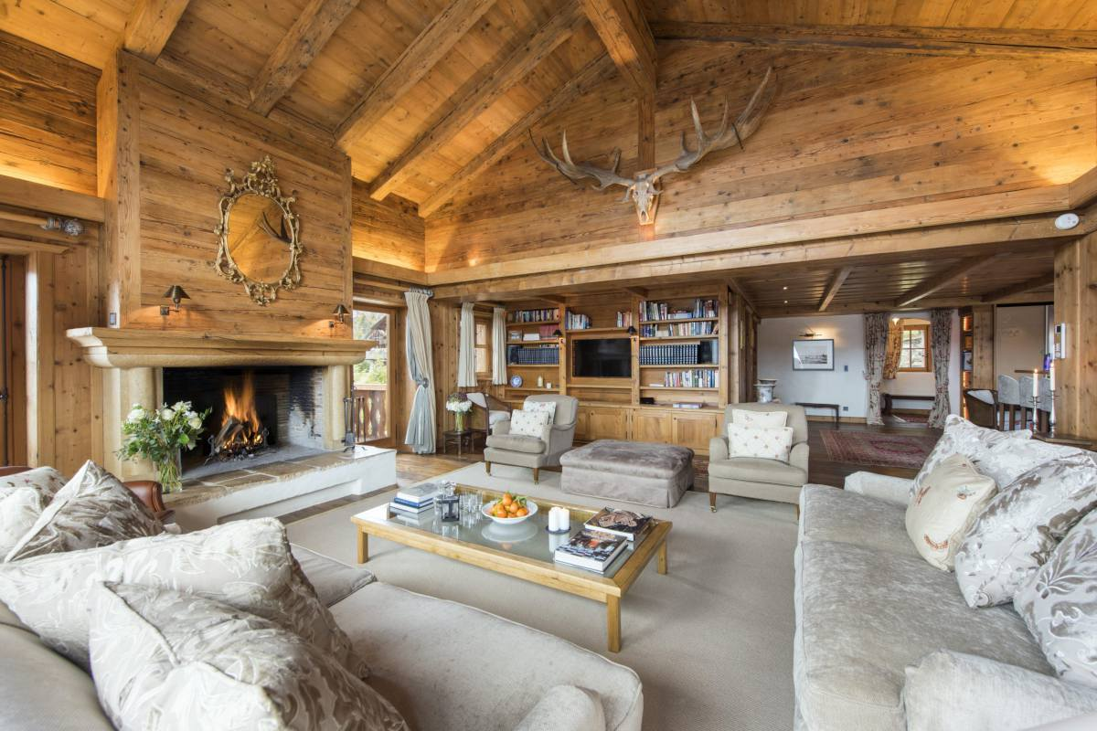 Open-plan living area with library corner and stone fireplace at Chalet Bella Coola in Verbier