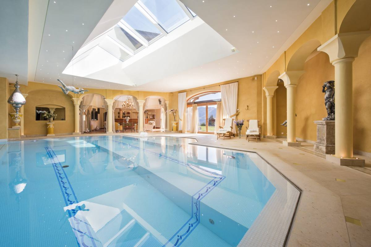 Spa with indoor swimming pool and doors opening onto garden at Chalet Bella Coola in Verbier