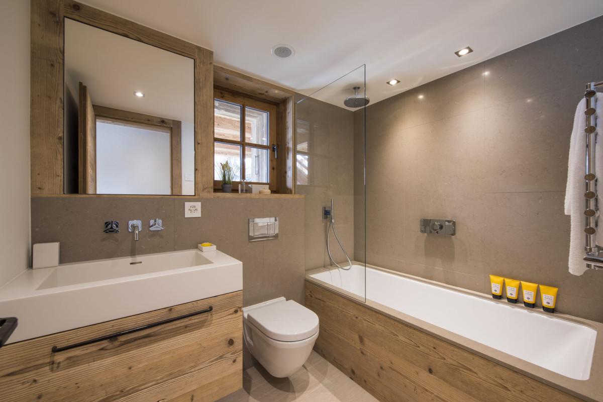 Ensuite bathroom with bath tub at Chalet Bioley in Verbier