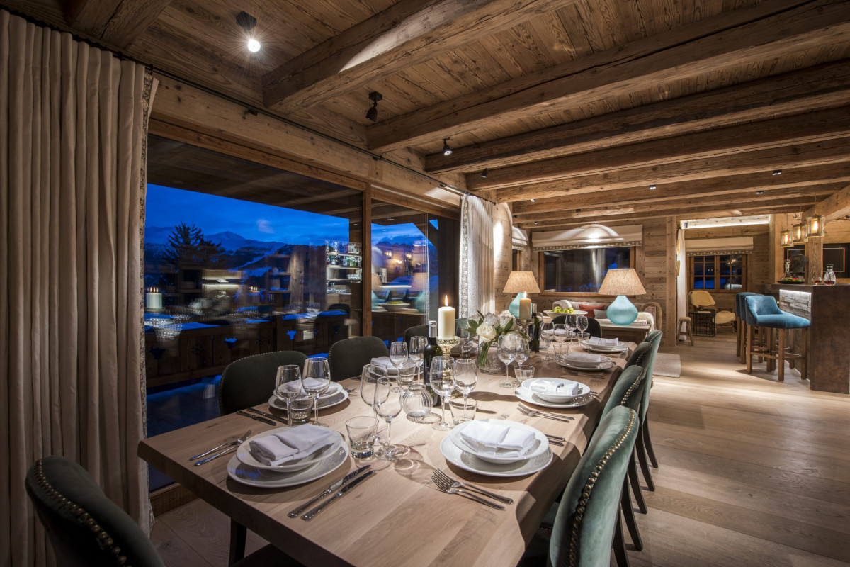 Evening dining table to lounge views at Chalet Bioley in Verbier