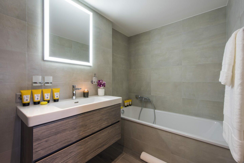 Ensuite bathroom with bath tub at chalet Daphne in Verbier