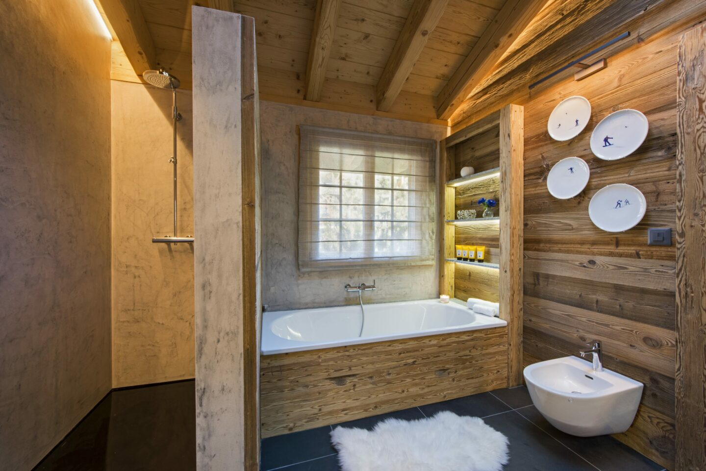 Ensuite bathroom with shower and bath tub at Chalet Daphne in Verbier