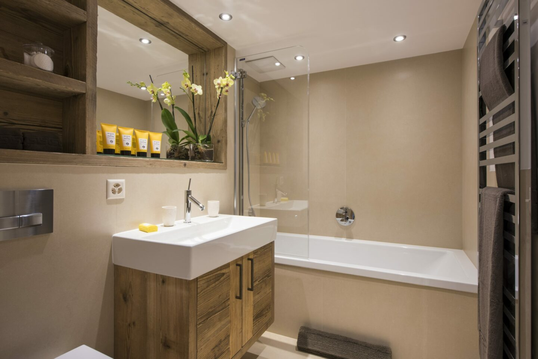 Ensuite bathroom with bath tub at Chalet Delormes in Verbier