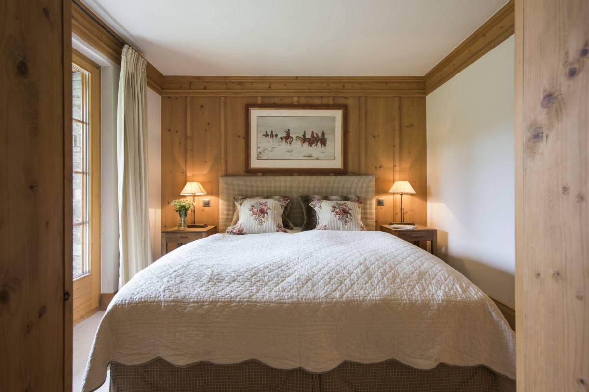 Ground floor double bedroom with doors leading to garden at Apartment Ivouette in Verbier