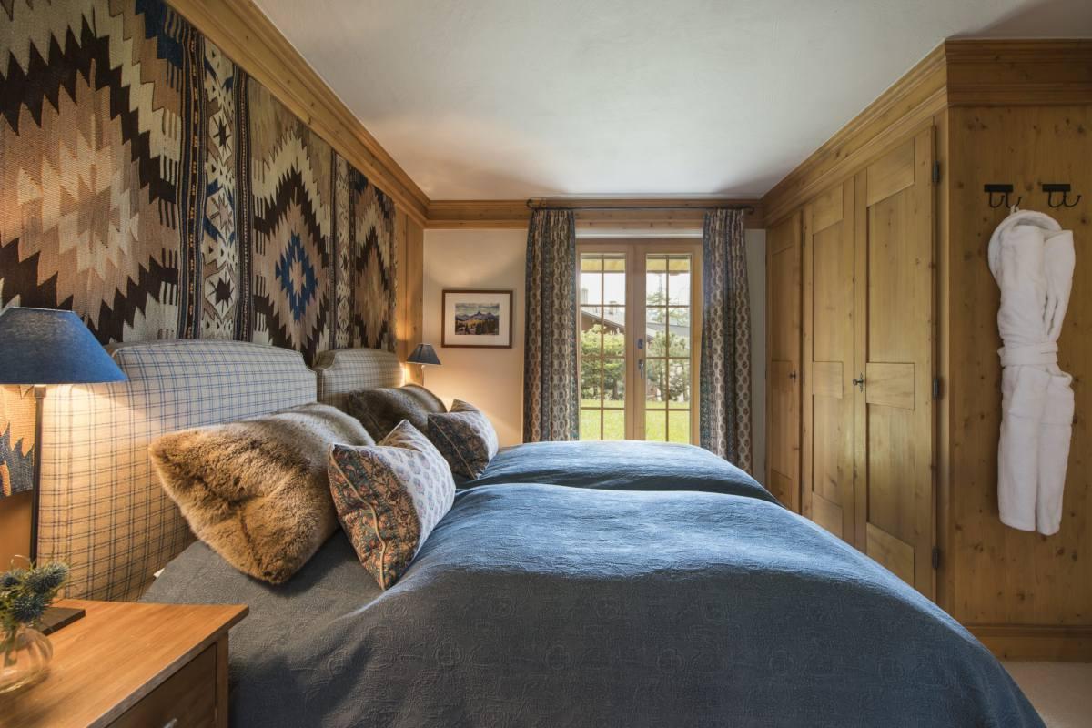 Ground floor double/twin bedroom with doors opening onto garden at Apartment Ivouette in Verbier