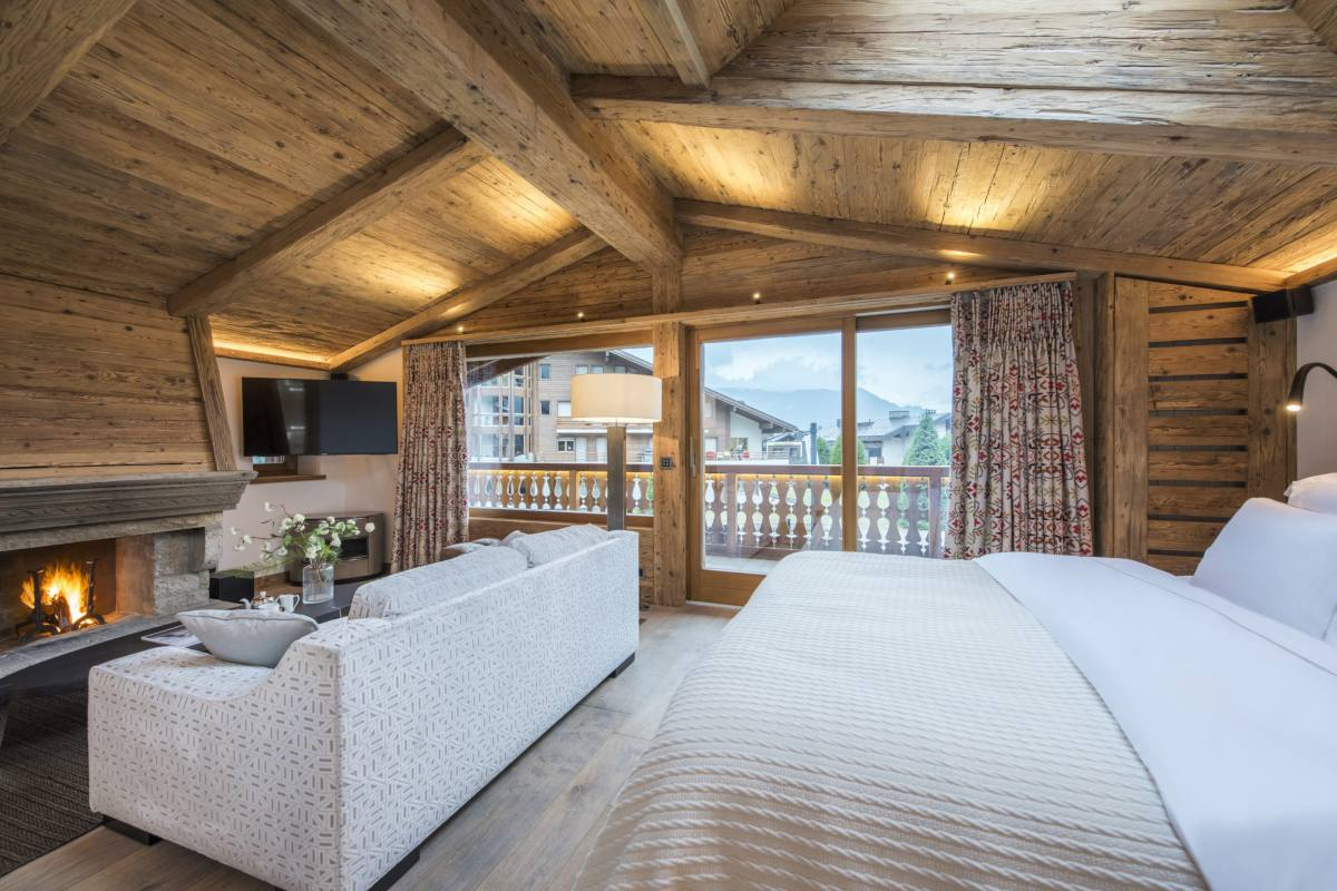 Master bedroom with sofa in front of wood burning fireplace at Chalet La Datcha in Verbier