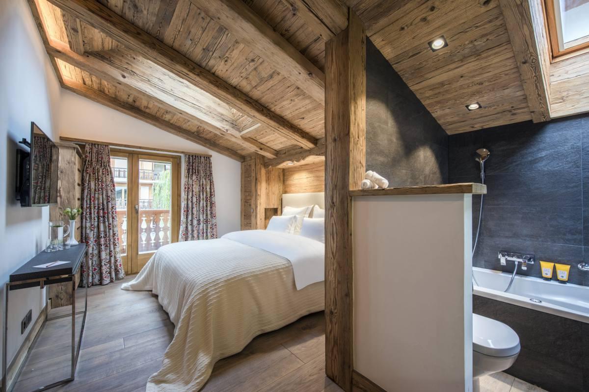 Top floor double bedroom with view into en suite bathroom at Chalet La Datcha in Verbier