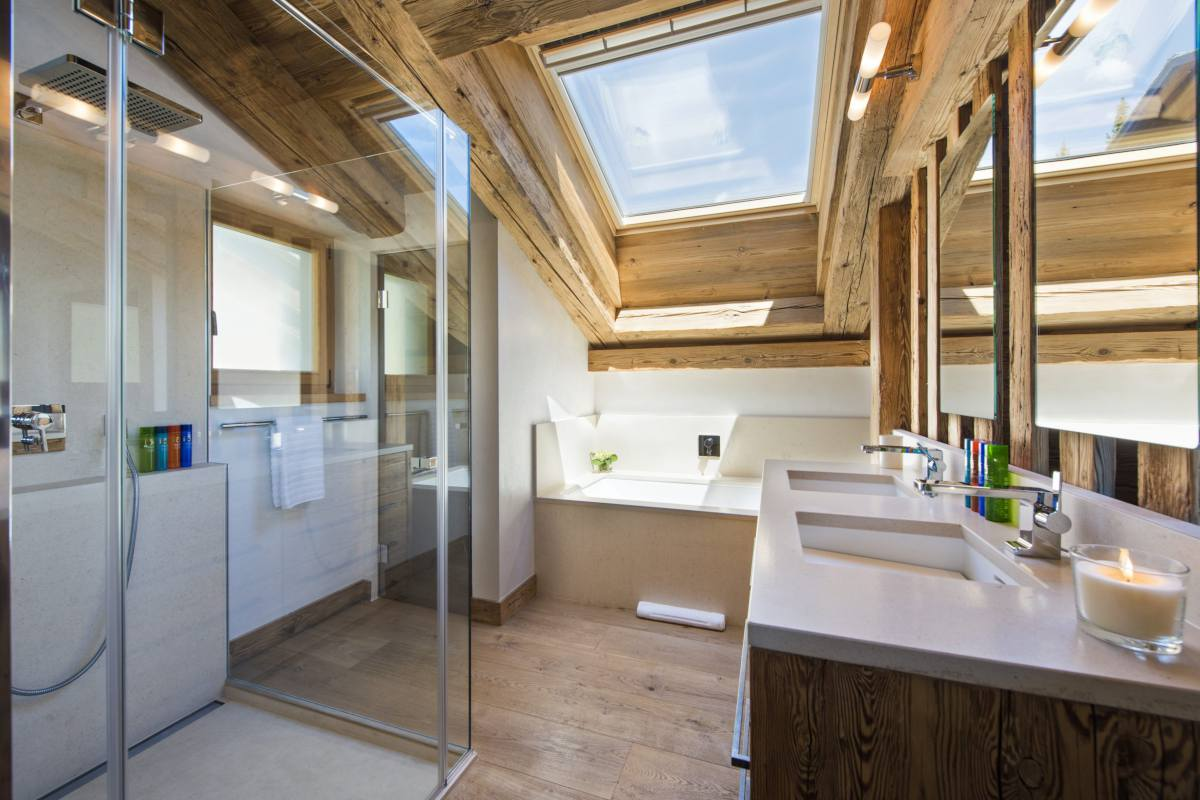 Master bathroom with glass-walled shower and bathtub at Chalet La Vigne in Verbier