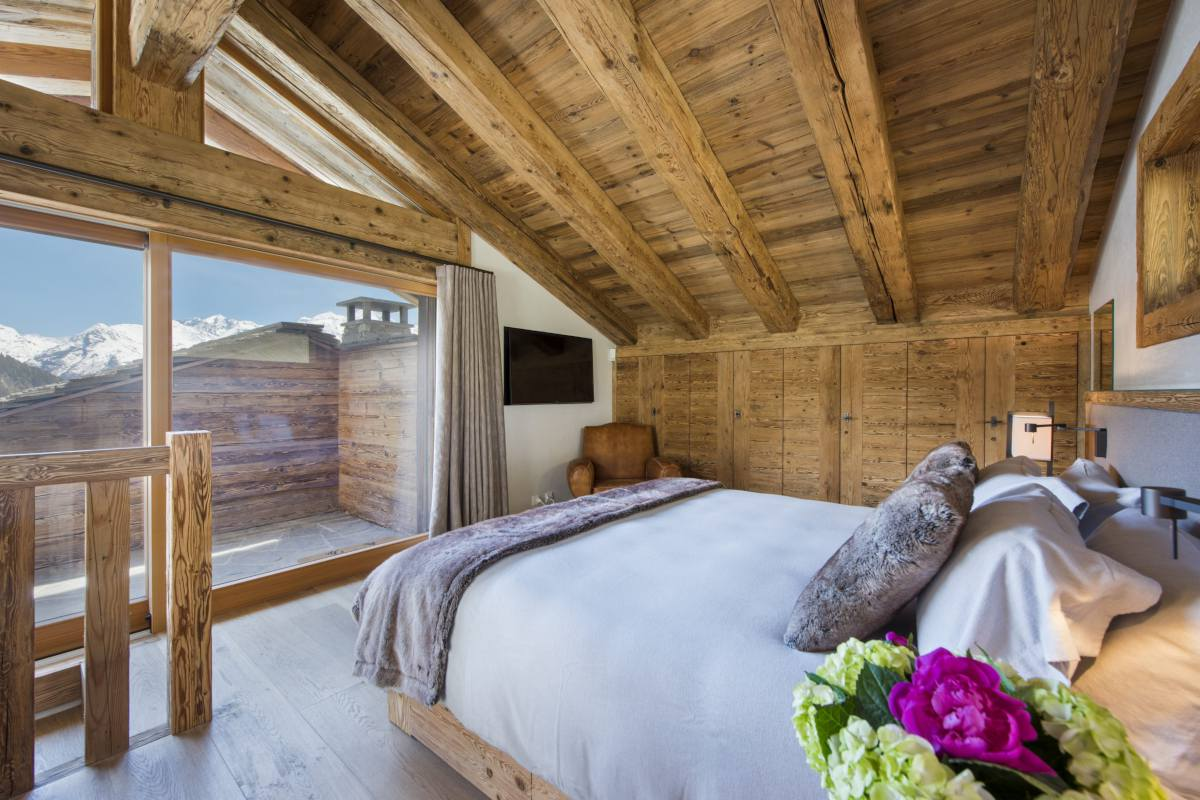 Master bedroom with private balcony at Chalet La Vigne in Verbier