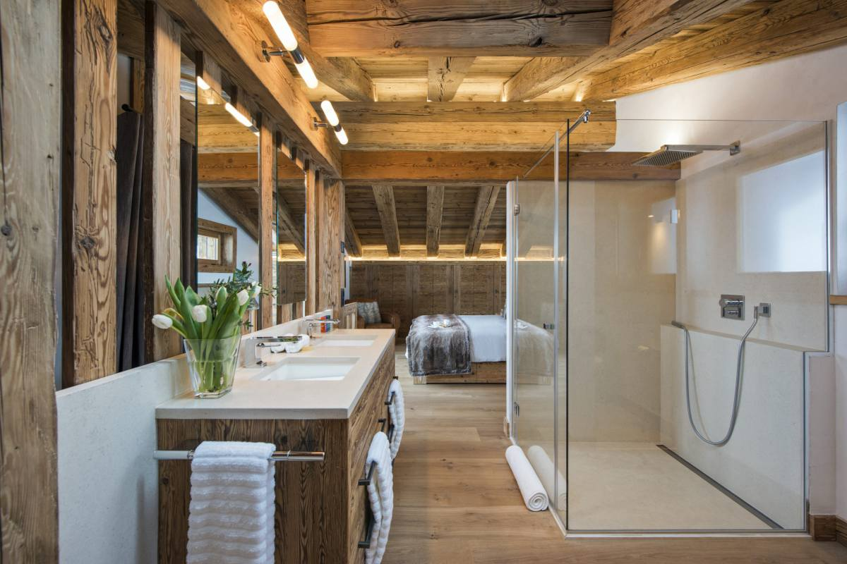 Master bedroom with glass-walled shower at Chalet La Vigne in Verbier