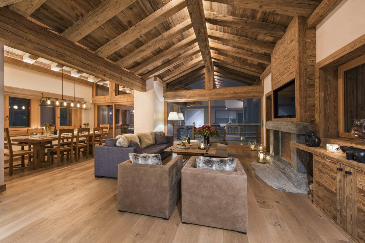 Open-plan living and dining area at night at Chalet La Vigne in Verbier