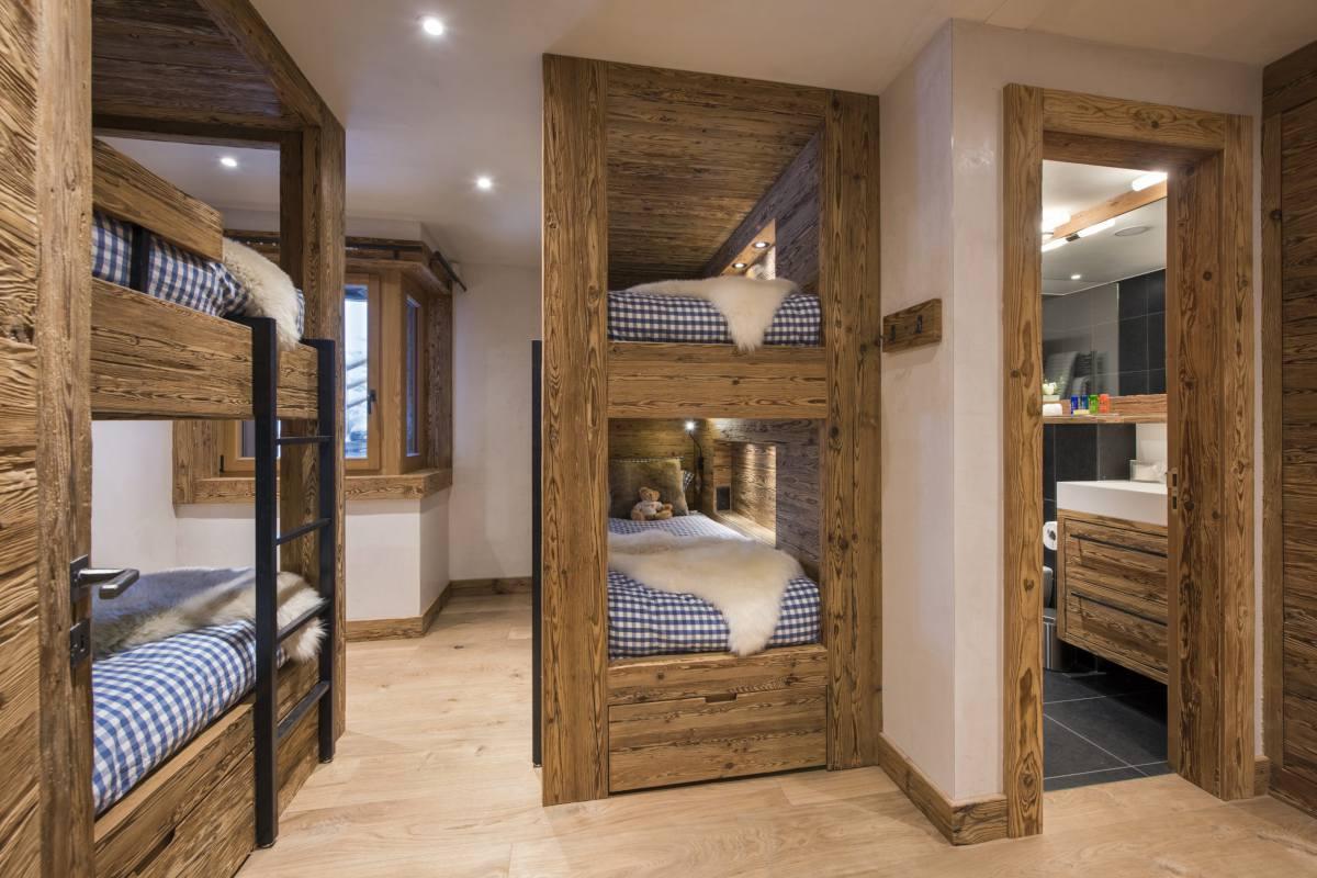 Quad bunk room with view into en suite shower room at Chalet La Vigne in Verbier