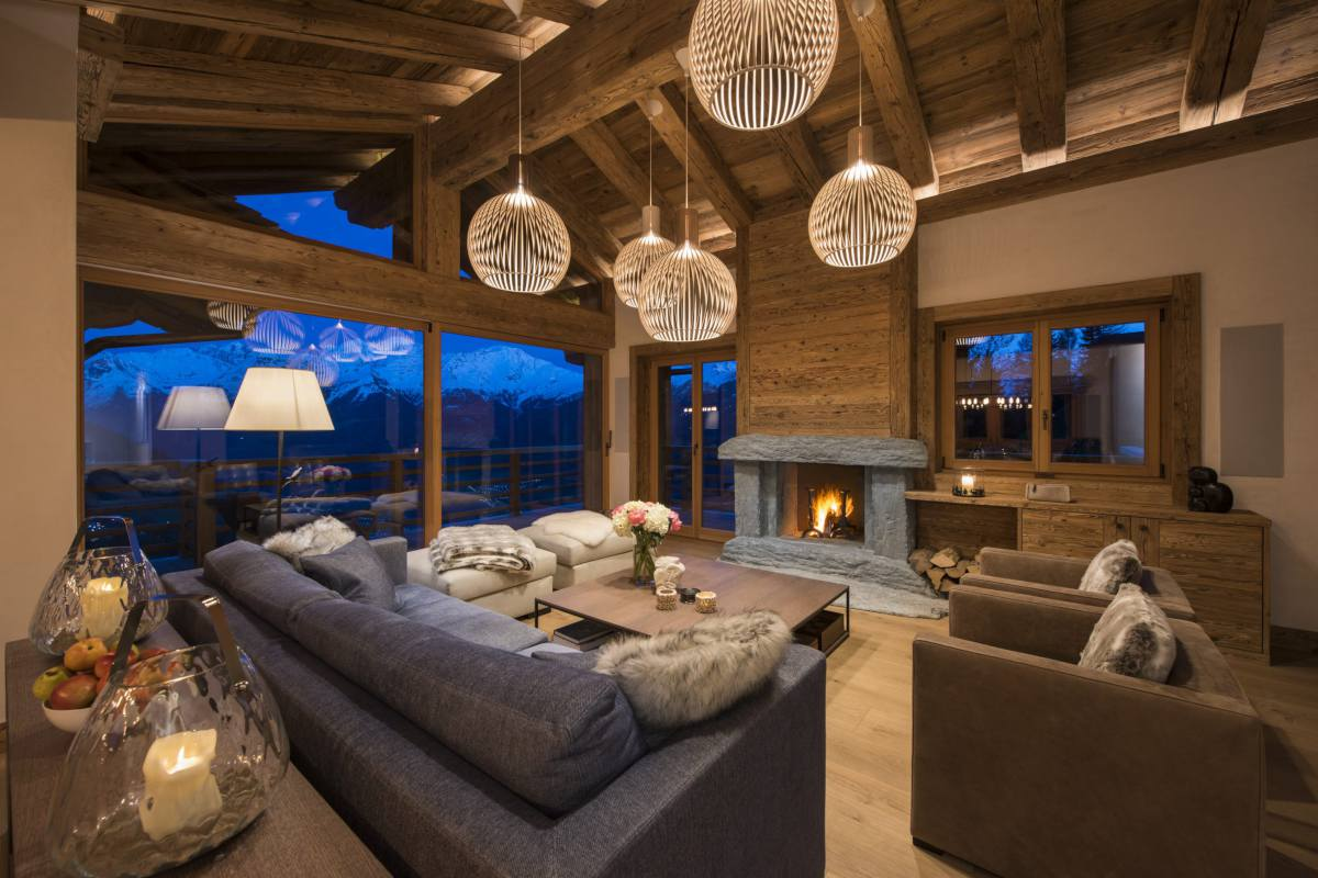 Living room at night with fireplace and mountain views at Chalet La Vigne in Verbier