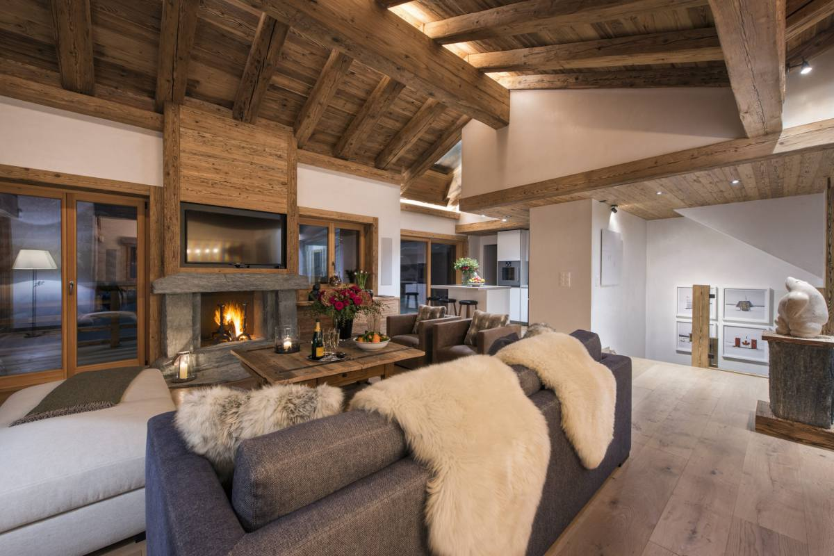 Living area at night with sofas in front of the fireplace at Chalet La Vigne in Verbier