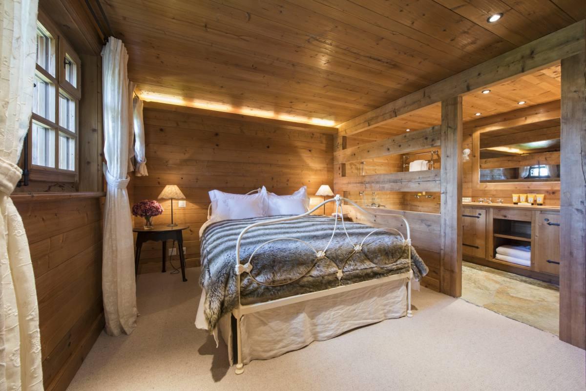 Ground floor master bedroom with view into en suite bathroom at Chalet Le Ti in Verbier