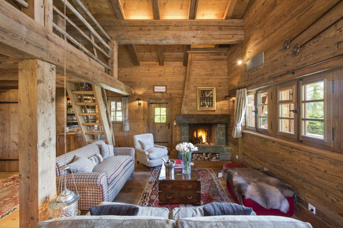 Top floor living area with stone fireplace and mezzanine at Chalet Le Ti in Verbier