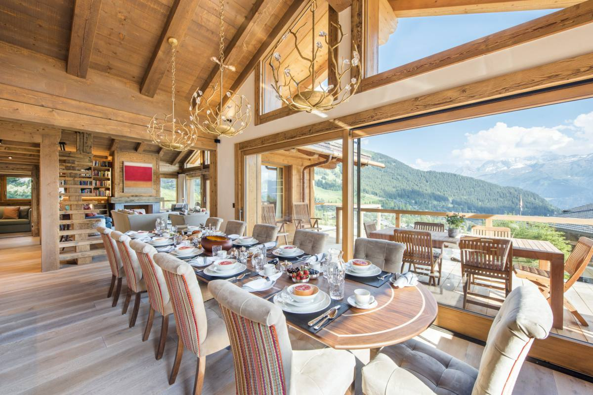 Dining table with view onto terrace with al fresco dining area at Chalet Les Etrennes in Verbier