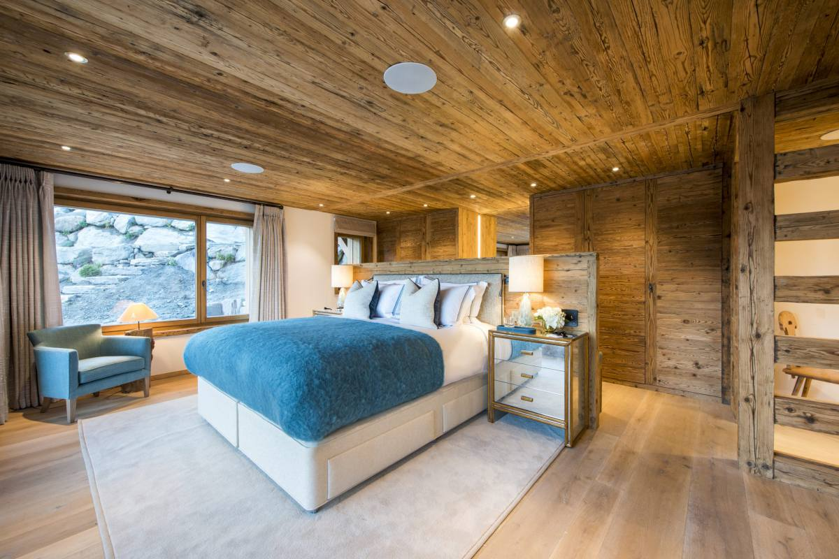 Master bedroom with large picture window at Chalet Les Etrennes in Verbier