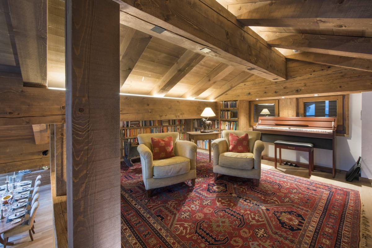 Mezzanine level with armchairs and library corner at Chalet Les Etrennes in Verbier