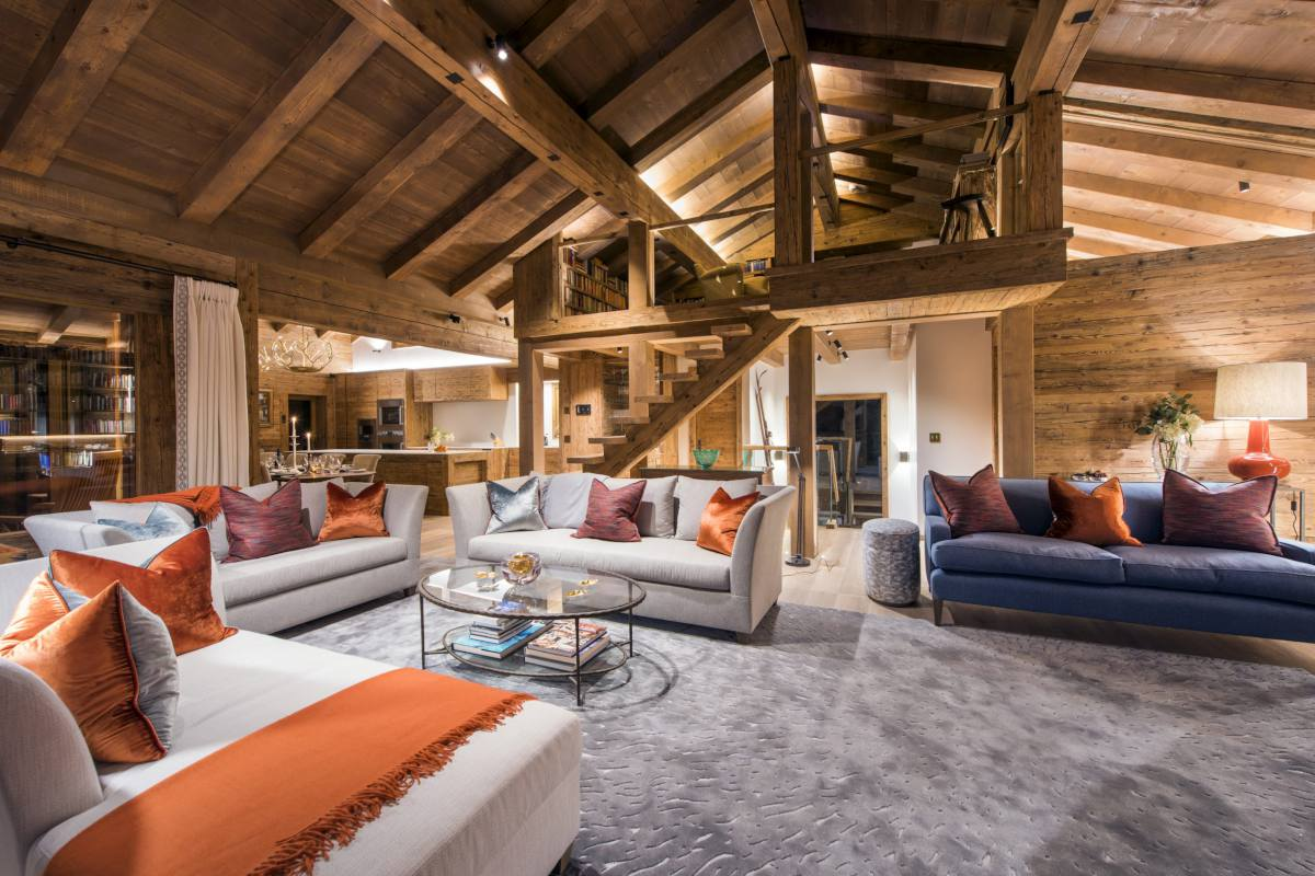Open-plan living area with stairs up to mezzanine level at Chalet Les Etrennes in Verbier
