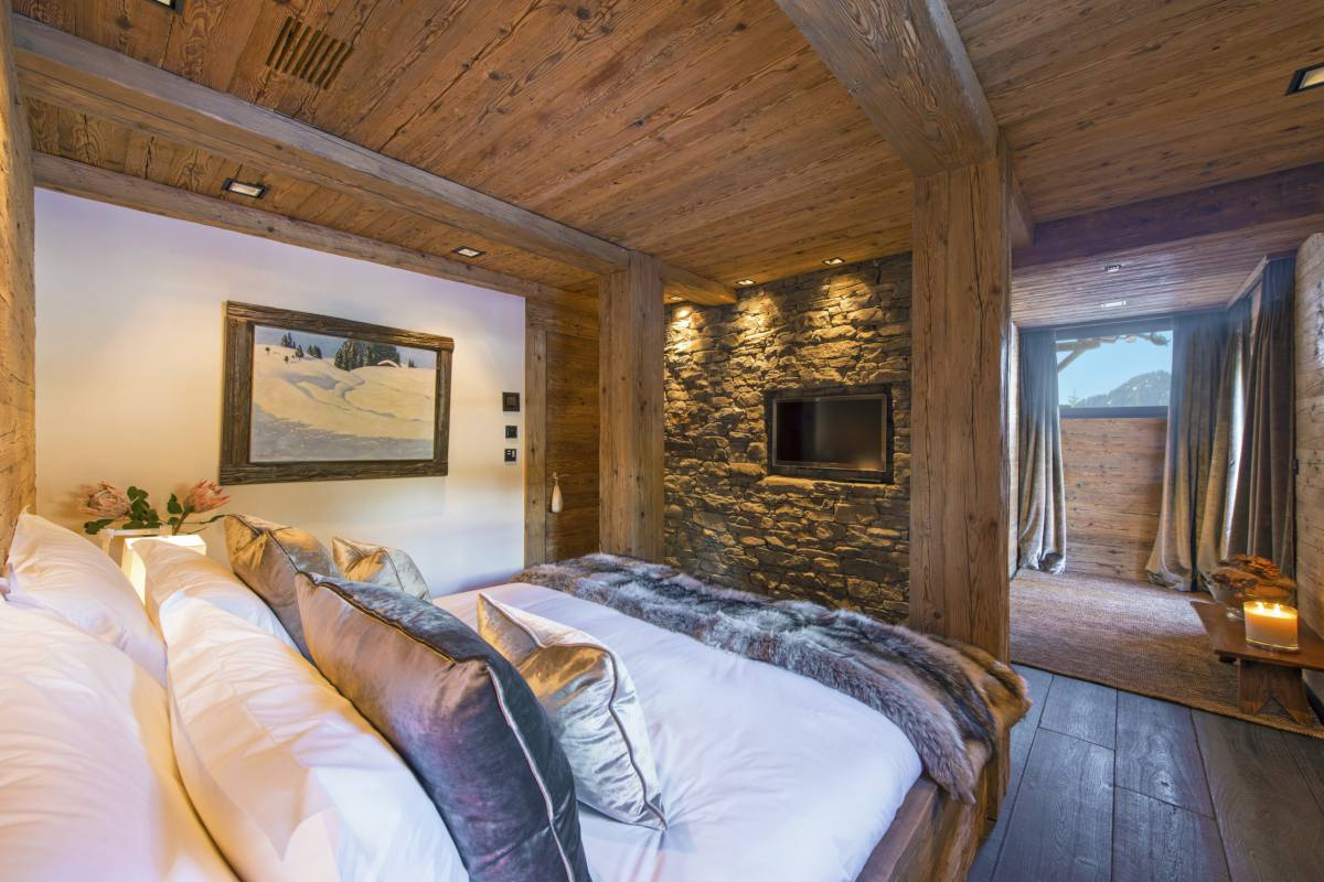 Double bedroom with TV and exposed stone wall at Chalet Makini in Verbier