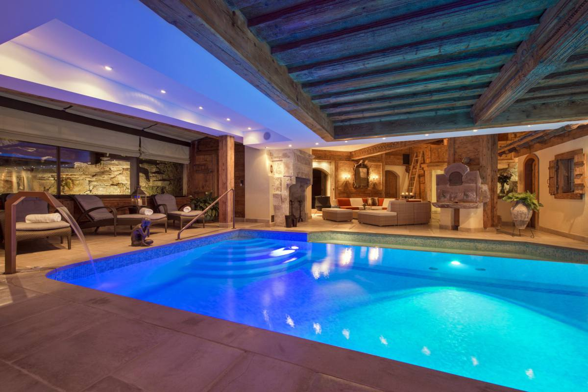 Indoor swimming pool and poolside lounge at Chalet Makini in Verbier