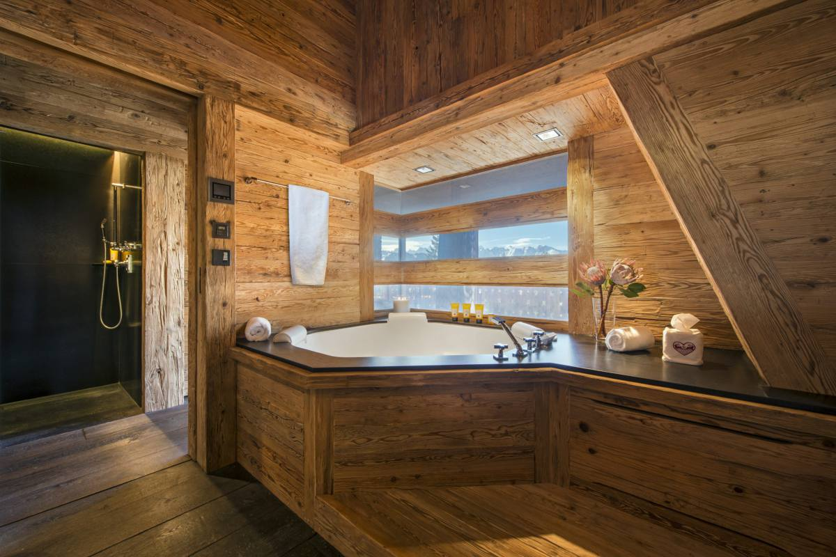 Master bathroom with corner bathtub and separate shower at Chalet Makini in Verbier