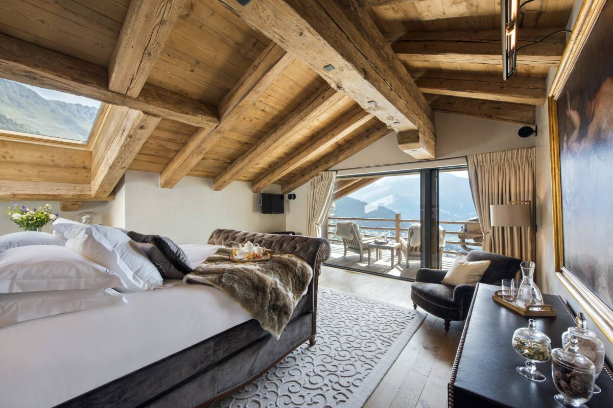 Master bedroom with balcony and mountain views at Chalet Norte in Verbier