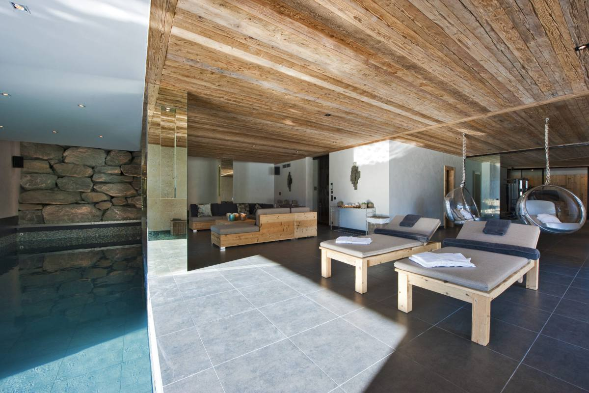 Poolside lounge with swing seats at Chalet Norte in Verbier