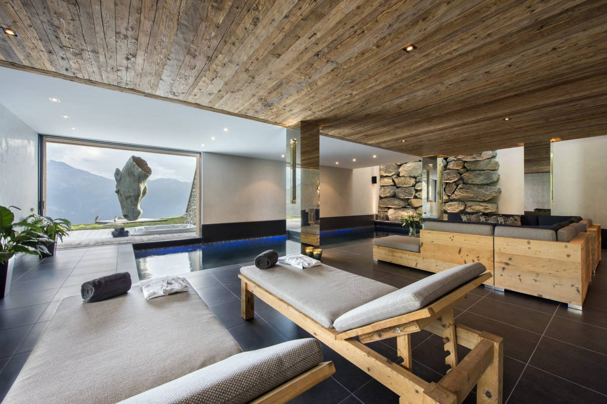Poolside lounge with view of horse sculpture at Chalet Norte in Verbier