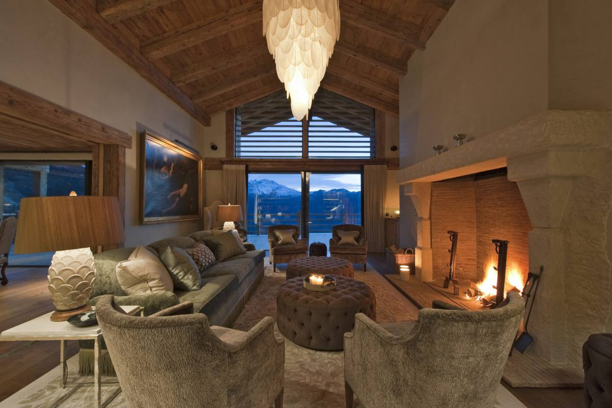 Sitting room with stone fireplace and mountain views at Chalet Norte in Verbier