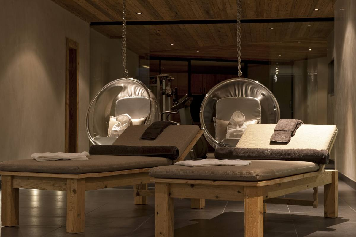 Spa area with loungers and swing seats at Chalet Norte in Verbier