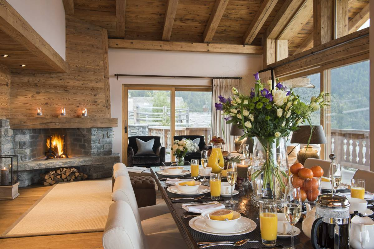 Breakfast table and corner fireplace at Chalet Sirocco in Verbier