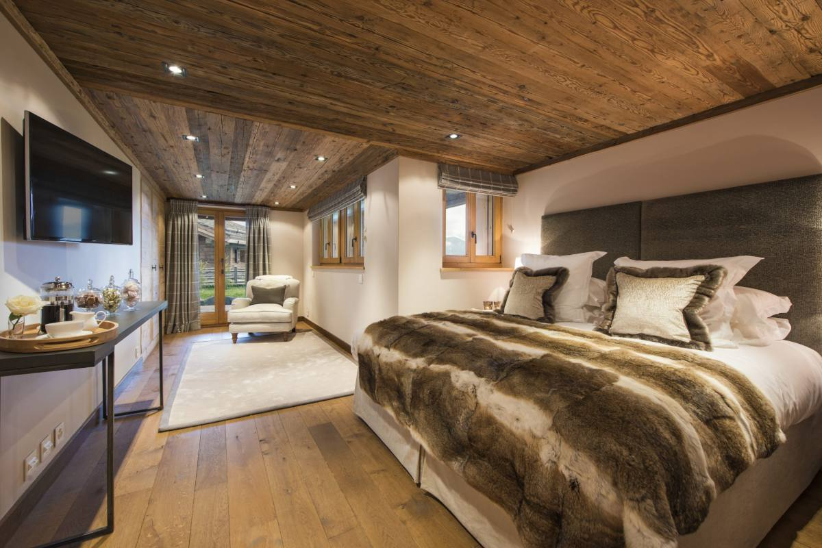 Double/twin bedroom with TV, sitting area and terrace access at Chalet Sirocco in Verbier