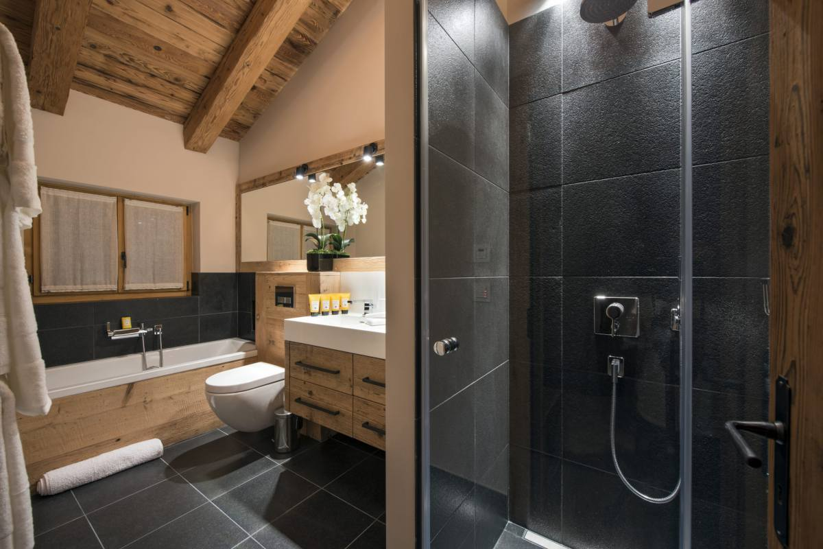 En suite bathroom with bathtub and separate shower at Chalet Sirocco in Verbier