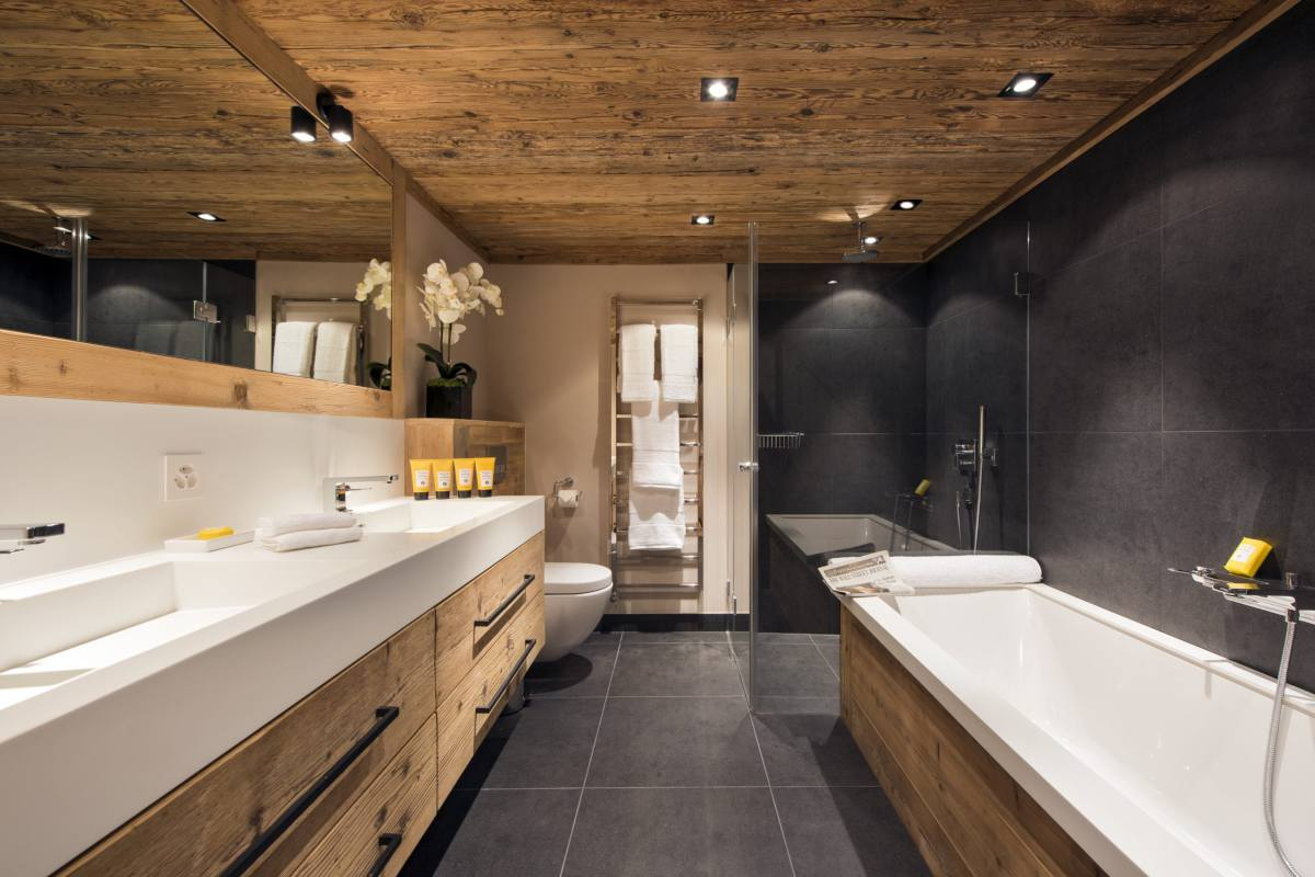 Master bathroom with bathtub, separate shower and double sinks at Chalet Sirocco in Verbier