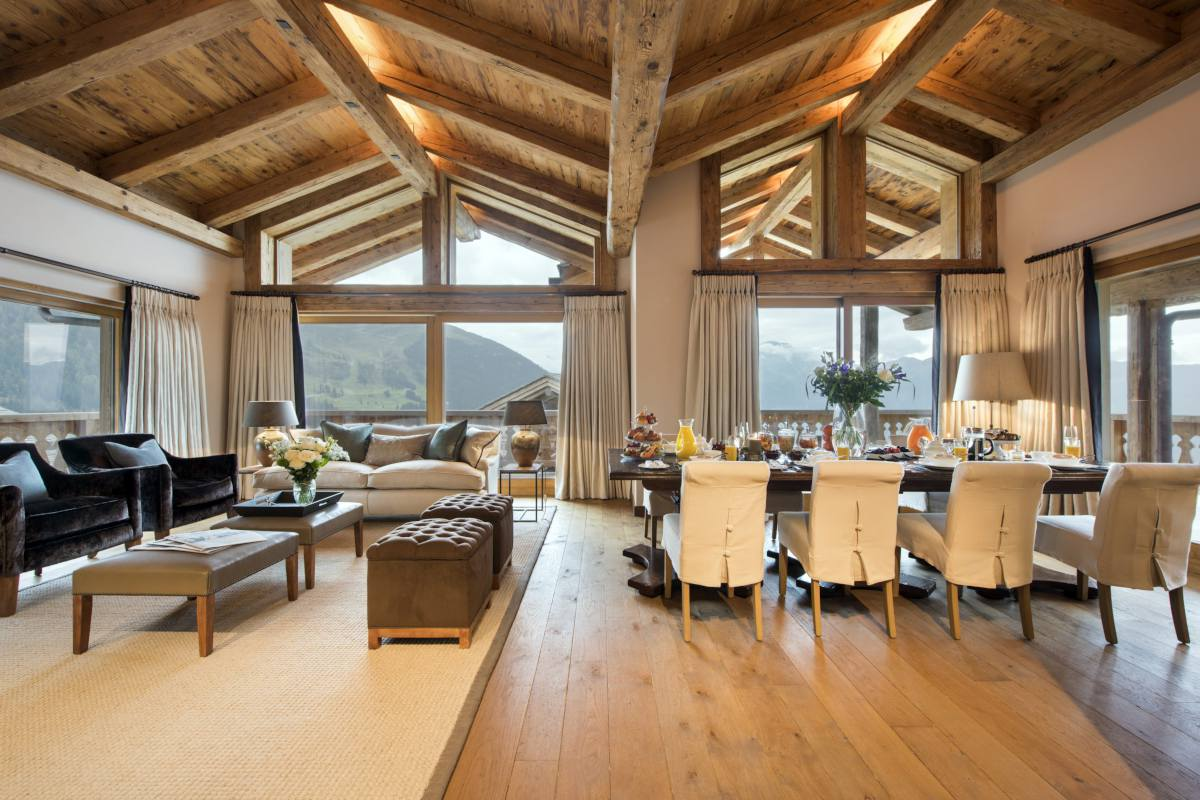 Open-plan living and dining area with large windows framing mountain views at Chalet Sirocco in Verbier