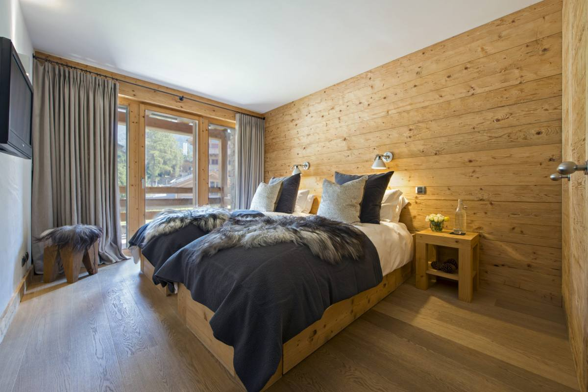 Double-twin bedroom with balcony access at Apartment Victoria 111 in Verbier