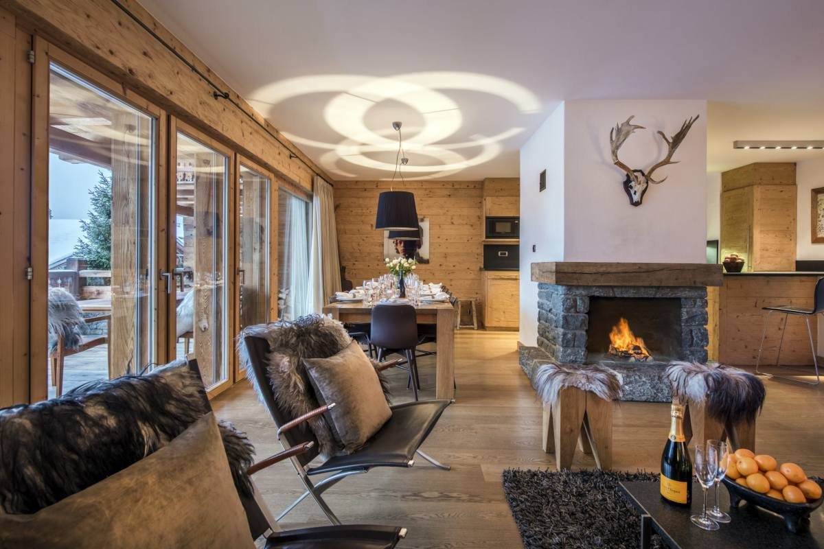 Stone fireplace in open-plan living area at Apartment Victoria 111 in Verbier