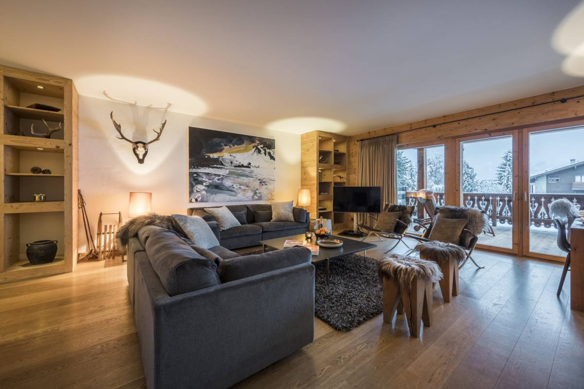 TV corner and balcony access from the living area at Apartment Victoria 111 in Verbier