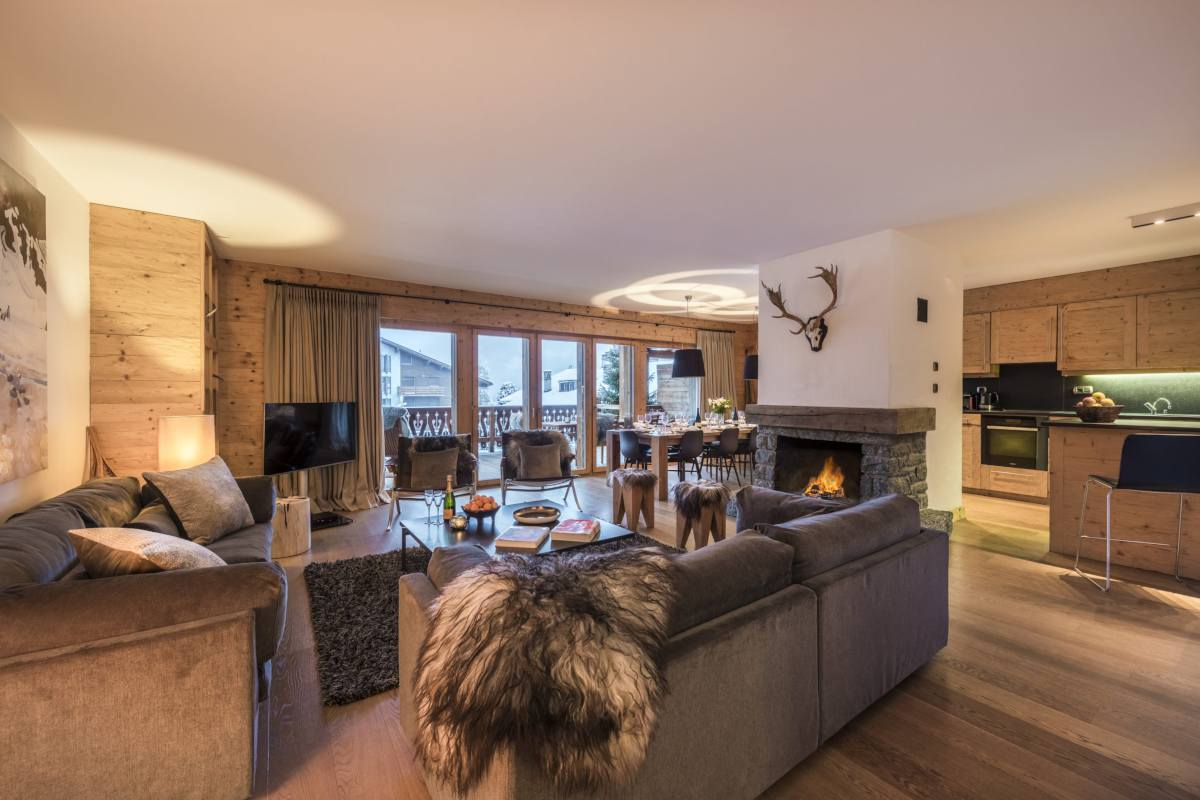 Open-plan living area with stone fireplace at Apartment Victoria 111 in Verbier