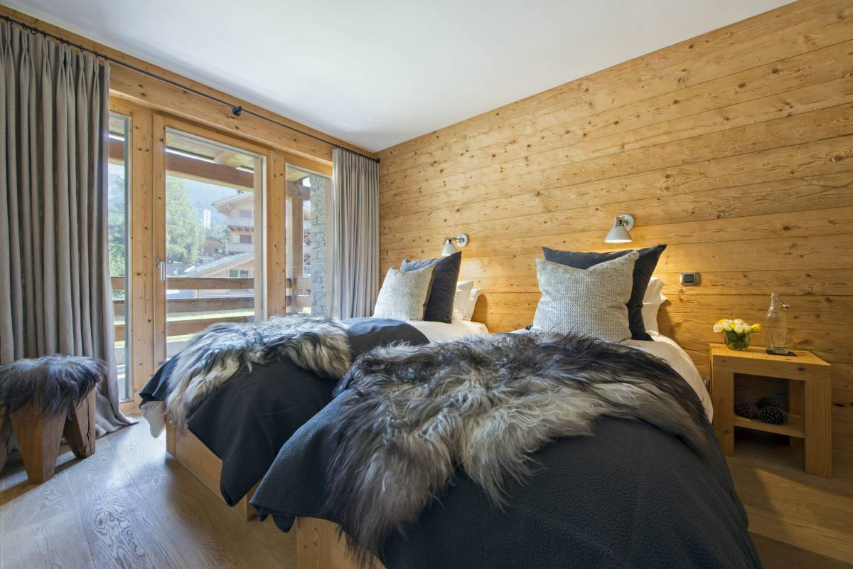 Twin bedroom with balcony access at Apartment Victoria 111 in Verbier