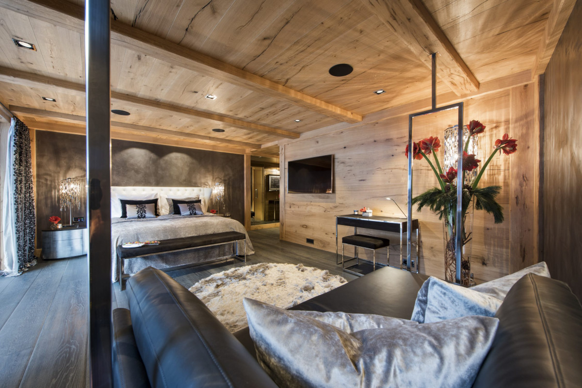 Master bedroom and relaxation space with shared balcony at Chalet Aconcagua in Zermatt