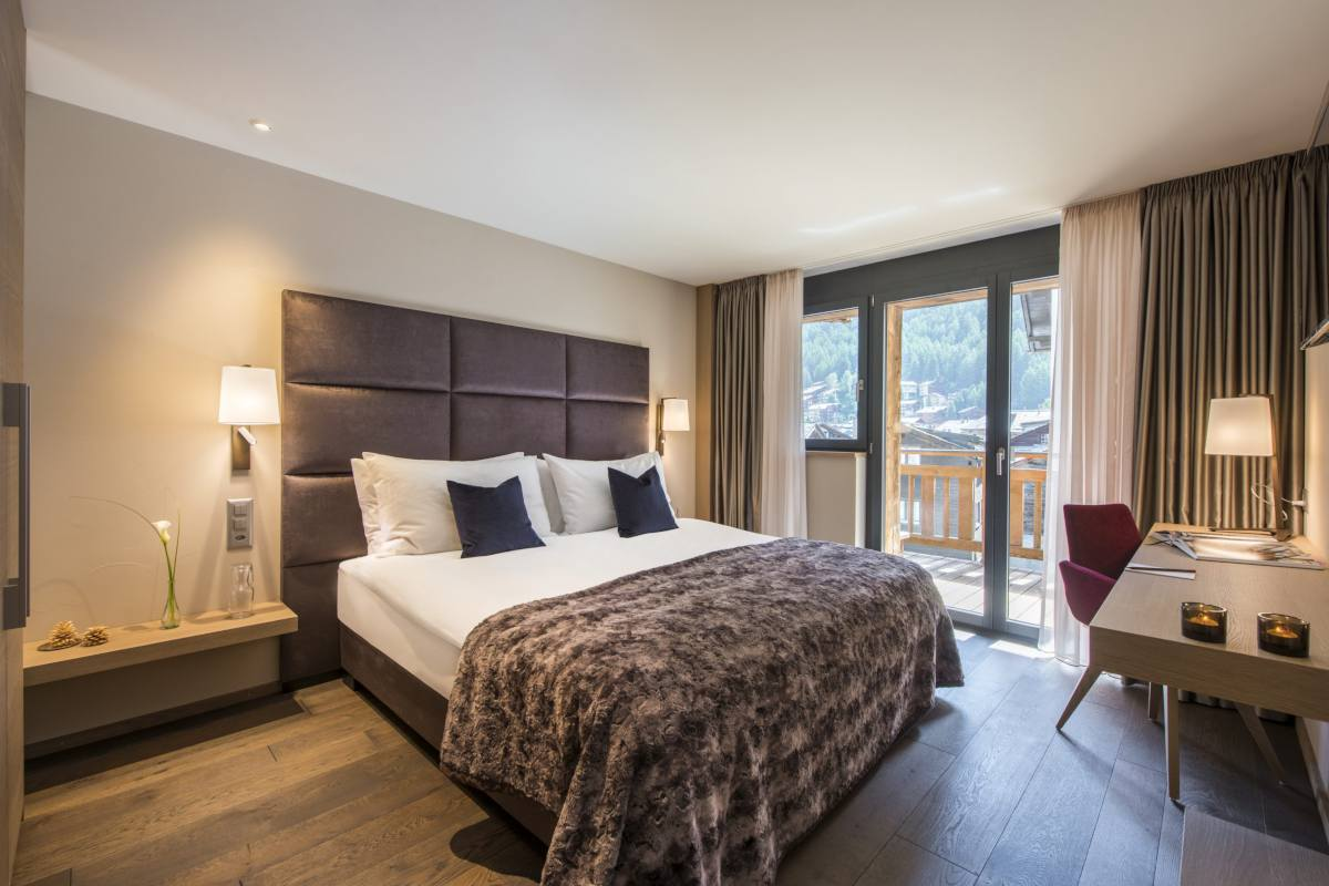 Double/twin bedroom with balcony access at Christiania Apartment 5 in Zermatt