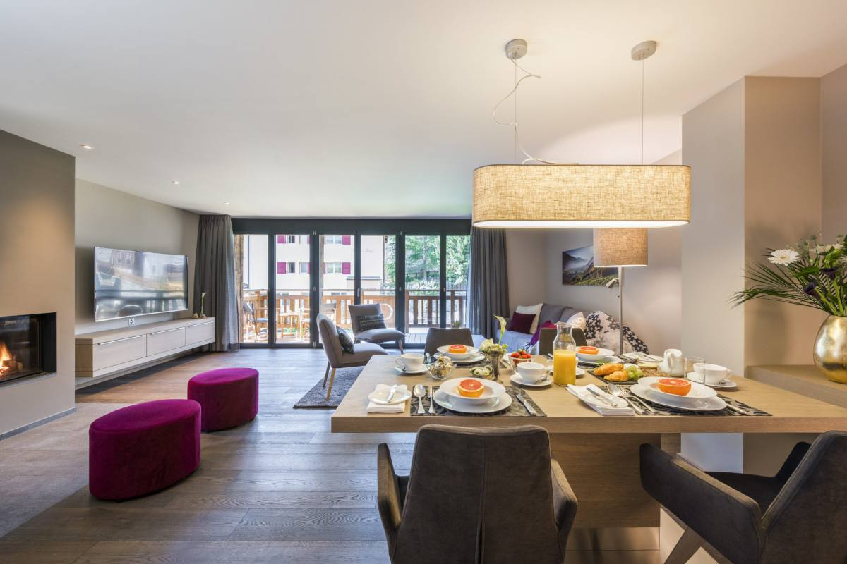 Open-plan living area with dining table set for breakfast at Christiania Apartment 5 in Zermatt