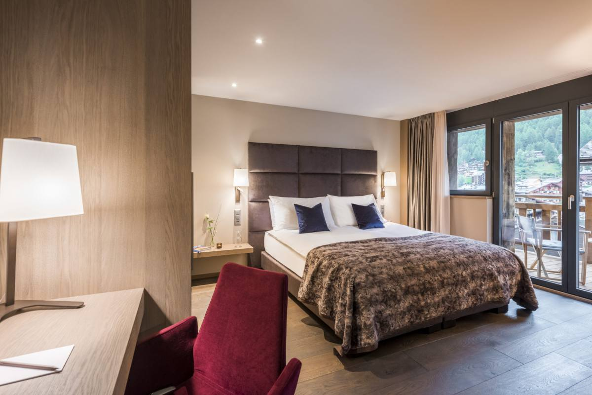Double/twin bedroom with desk and shared balcony at Christiania Apartment 7 in Zermatt